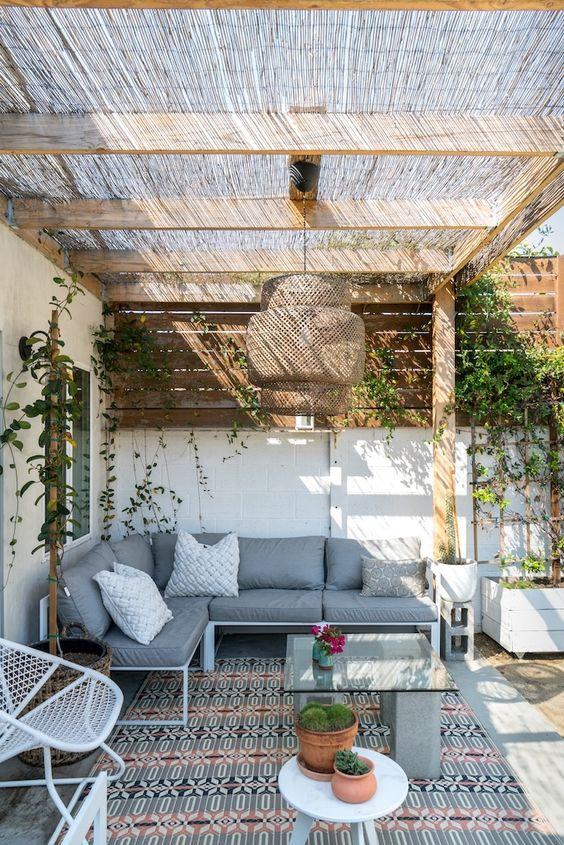un luminoso cortile boho con un divano ad angolo, alcune sedie in metallo, un tavolo in cemento e marmo, una lampada a sospensione in vimini e un po 'di verde sulle pareti
