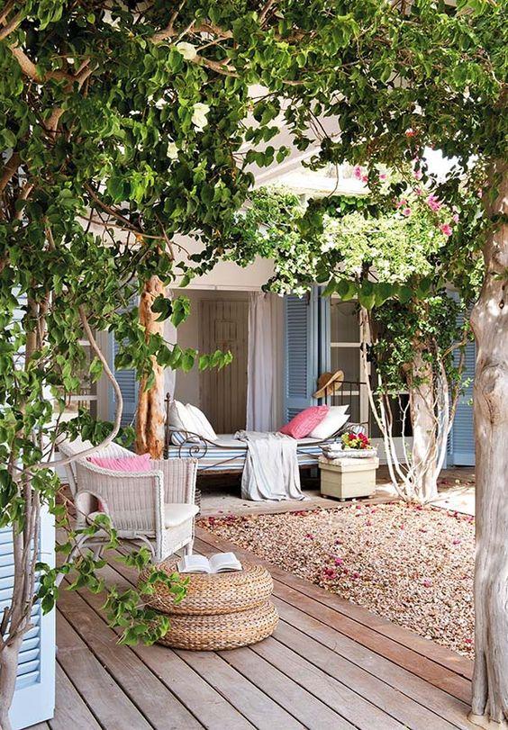 una fresca oasi nel patio con alcuni alberi, viti, un divano letto vintage e oggetti in rattan più lenzuola color pastello