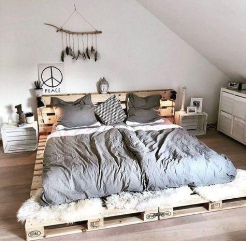 un semplice letto a pallet basso con testiera, con finta pelliccia ai piedi e comodini a cassa per un match