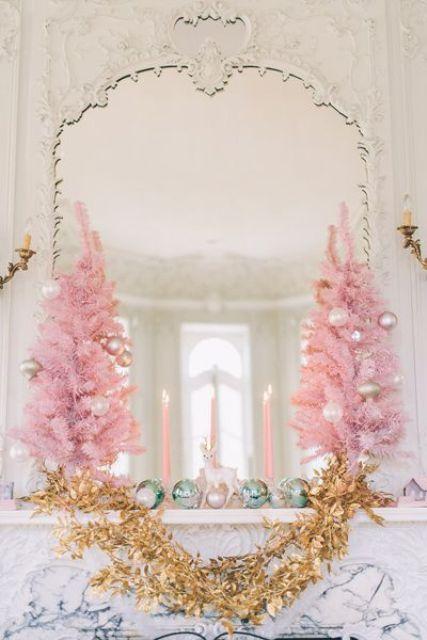 mini alberi di Natale rosa con ornamenti metallici e pastello e candele rosa rendono la mensola del camino super raffinata