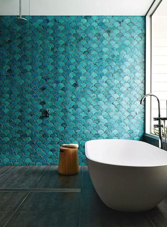 un muro di piastrelle in scala di pesce turchese rende lo spazio simile a una sirena, e una vasca serena si aggiunge ad esso