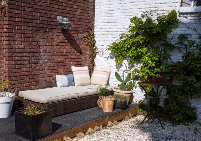 un piccolo terrazzo scuro con una panca imbottita, piante in vaso, cactus e piante grasse, una lampada da parete e un tavolino