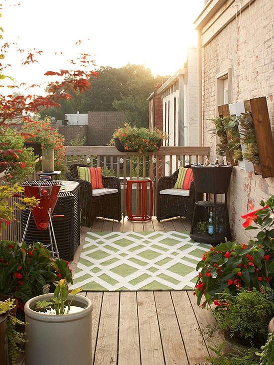 piccolo terrazzo scoperto e luminoso con mobili intrecciati semplici, tappezzeria colorata, una griglia e piante e fiori in vaso
