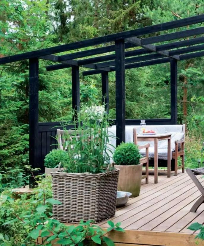 un piccolo terrazzo con un tetto sopra per appendere le tende, una confortevole sala da pranzo con semplici mobili in legno e piante in vaso