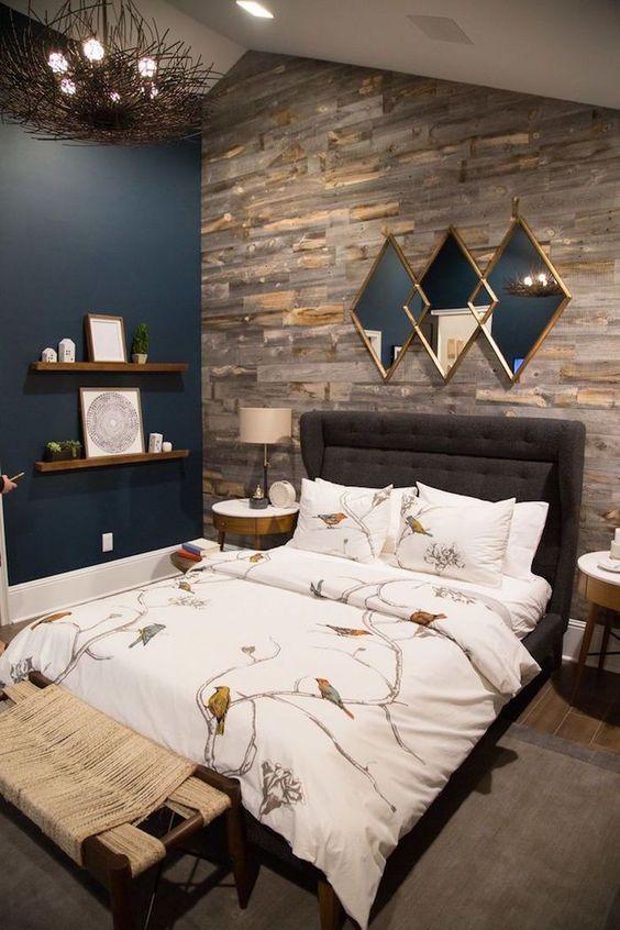 una lussuosa camera da letto con un muro con accento blu scuro, uno in legno di recupero e uno splendido specchio geometrico metallico