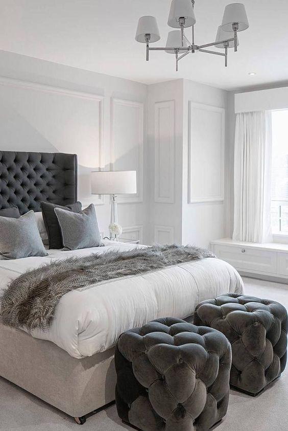 un paio di sgabelli trapuntati grigio grafite ai piedi del letto che si intonano al letto e ai tessuti