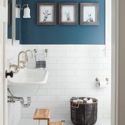 un bagno contemporaneo con pareti in parte dipinte di blu e in parte rivestite con piastrelle bianche