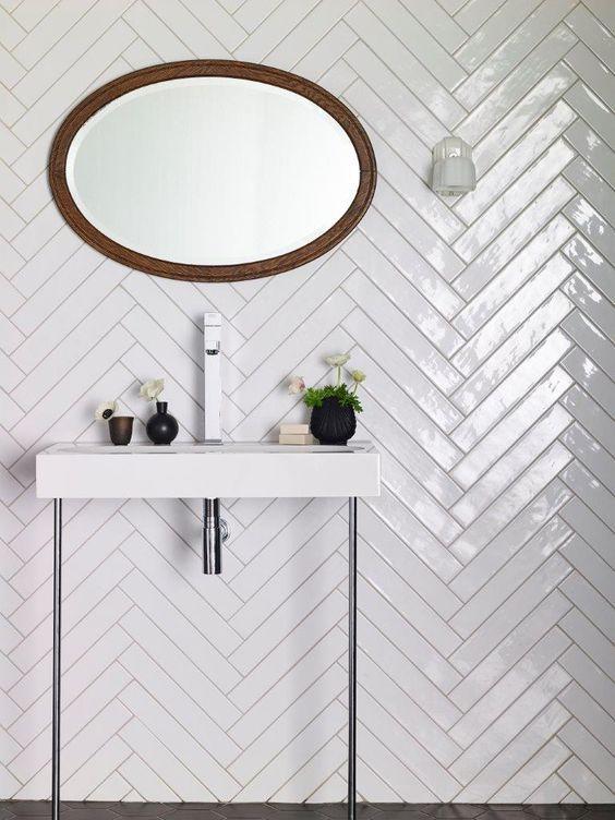 le piastrelle bianche lunghe e sottili rivestite con un motivo a chevron sono un'idea elegante, accentuano le piastrelle con malta a contrasto