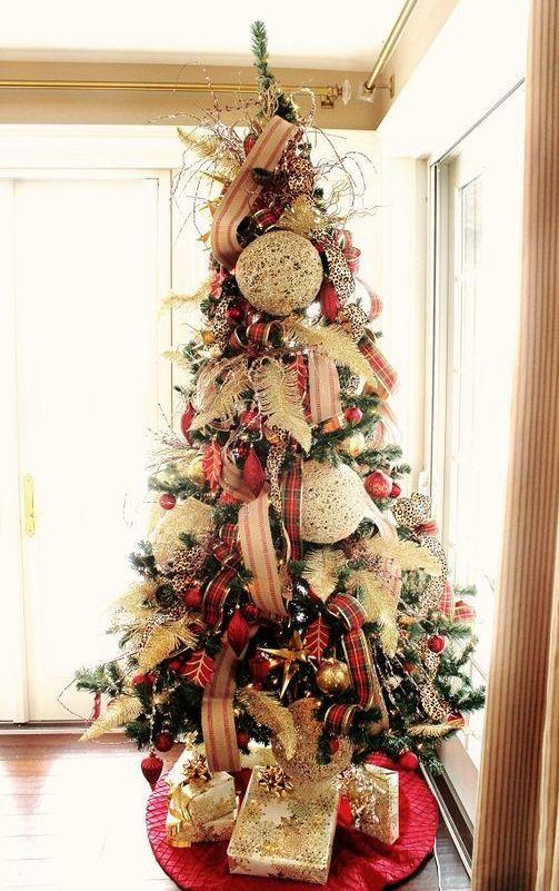 un albero di Natale audace e accattivante con nastri a righe e scozzesi, piume, ornamenti rossi e dorati e quelli bianchi oversize