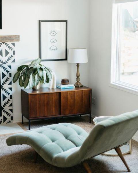 un lettino curvo color acqua posto vicino alla finestra è un bel pezzo per leggere e rilassarsi qui