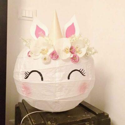 una splendida lampada da tavolo unicorno con fiori di carta realizzata con un paralume IKEA Regolit, un fai-da-te facile e carino