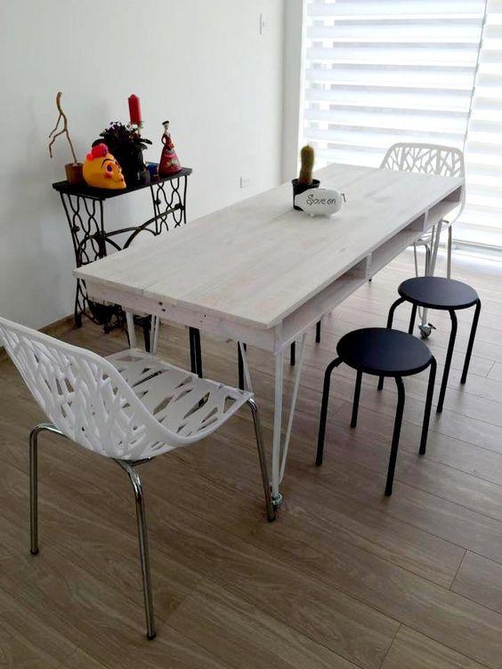 un rilassato tavolo da pranzo con pallet imbiancato con un piano di un unico pallet e sottili gambe in metallo su rotelle