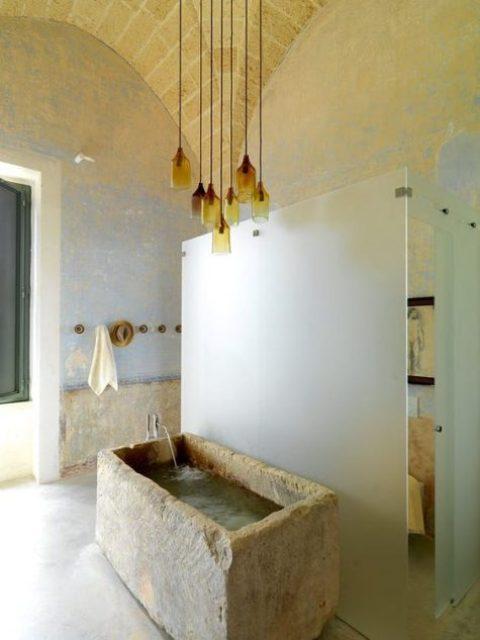 un bel bagno con una vasca in pietra grezza e un gruppo di lampade a sospensione in vetro ambra