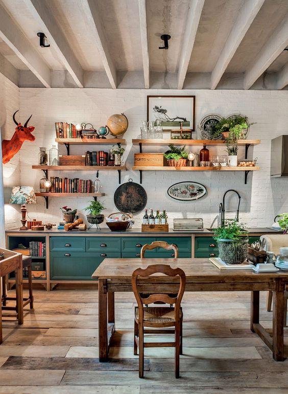 una luminosa cucina eclettica che abbina armadi verde acqua, mobili rustici in legno, piante in vaso e una finta testa di animale