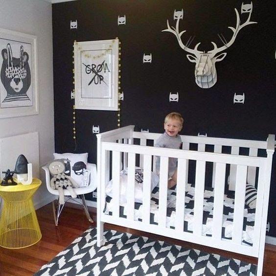 un muro con accento nero, un tappeto stampato e alcune fantastiche opere d'arte e giocattoli per mantenere la combinazione di colori