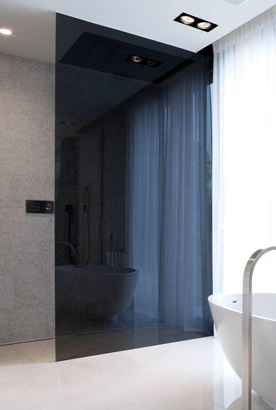 un bagno minimalista con una doccia in vetro fumé per separare lo spazio delicatamente e con una sensazione spigolosa