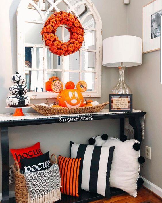 una luminosa console d'ingresso di Halloween con cuscini neri, bianchi e arancioni, una zucca di Halloween, una ghirlanda di zucca e una pila di zucche bianche