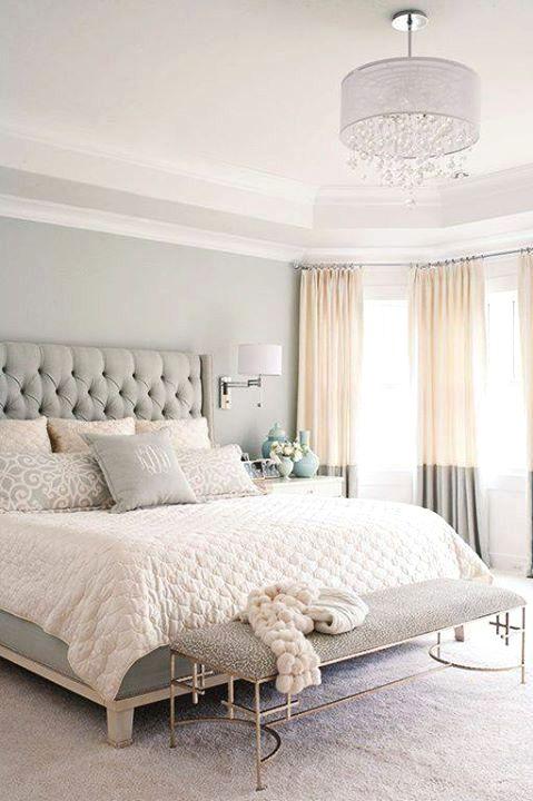 una camera da letto rilassante in grigio chiaro, con un letto imbottito, tende bicolore e un'elegante panca