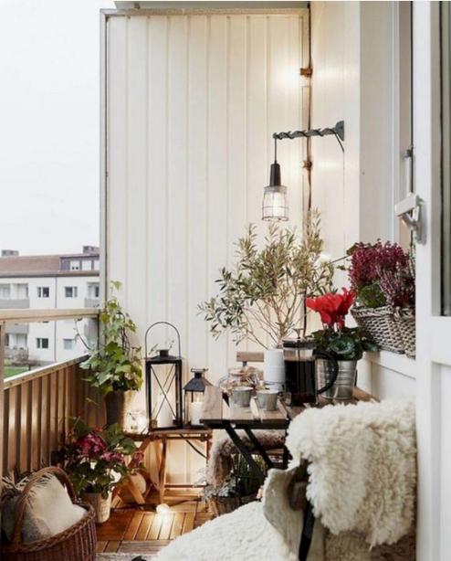 un balcone natalizio con lussureggianti fioriture luminose, vegetazione in vaso, lanterne a candela e finta pelliccia qua e là