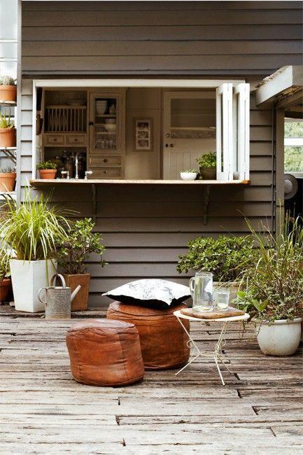 una finestra con cornice bianca pieghevole, un sottile ripiano del tavolo e alcuni pouf in pelle e un tavolino da caffè