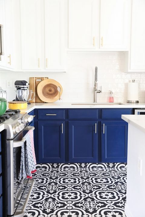 una cucina chic e audace con armadi blu scuro e piani di lavoro bianchi e piastrelle a mosaico blu scuro e bianche sul pavimento