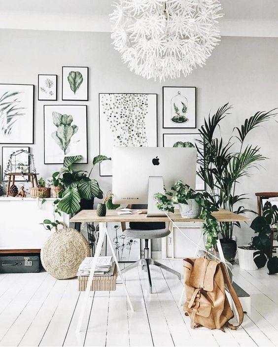 un ufficio-studio in casa neutro chic con una grande galleria a muro, piante in vaso, una scrivania a cavalletto e alcune valigie vintage