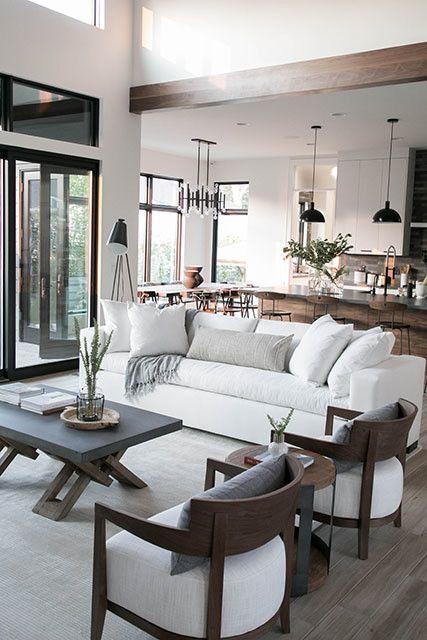 un moderno soggiorno neutro con un divano bianco come fulcro dello spazio e tutto il resto dei mobili intorno
