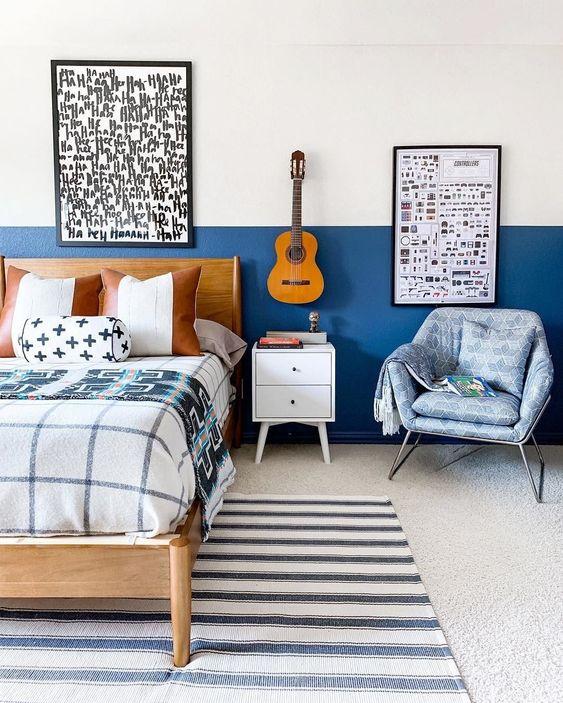 una piccola camera da letto realizzata con blocchi di colore blu mirtillo, opere d'arte grafiche e tessuti stampati dappertutto
