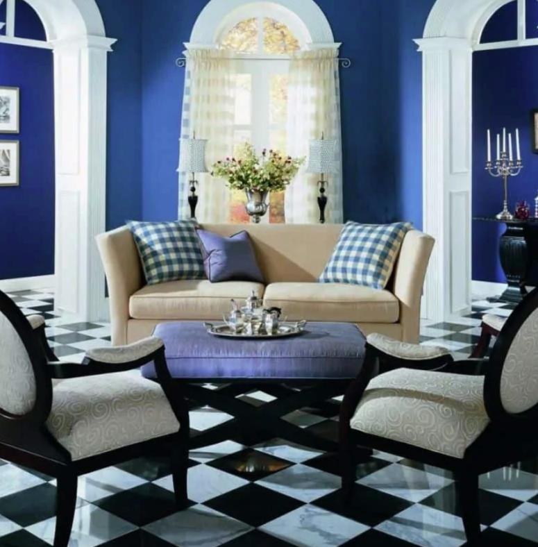 un piccolo soggiorno fatto in blu mirtillo, con un pavimento di piastrelle bianche e nere, varie stampe e finestre ad arco