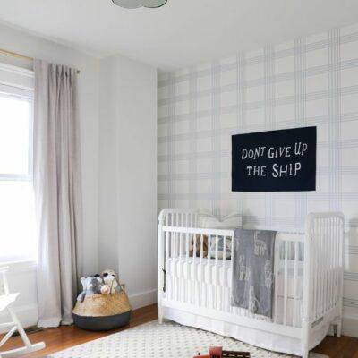 un asilo nido accogliente e luminoso con un muro a quadri con sfumature chiare e un divertente tappeto a pois bianco