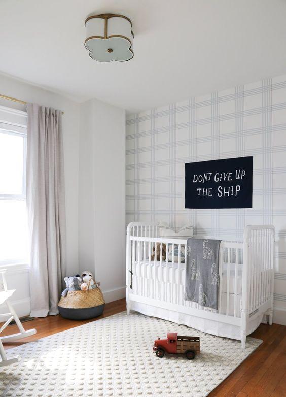 un cameretta accogliente e luminoso con un muro a quadri con sfumature chiare e un divertente tappeto a pois bianco