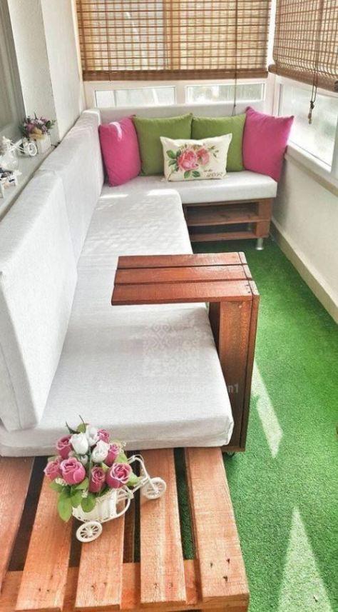 un tappeto verde brillante che ricorda l'erba, cuscini verdi e rosa e alcuni fiori per un moderno balcone primaverile