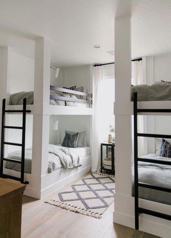 una camera per bambini neutra contemporanea con due letti a castello, scale in metallo e lampade da parete su ogni letto
