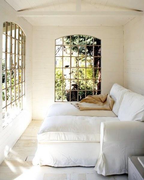 una piccola veranda sofisticata con comode poltrone e porte finestre che brilla di eleganza