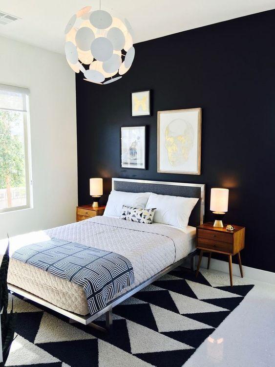 una camera da letto moderna della metà del secolo audace e drammatica con un muro blakc, un tappeto geometrico, un letto nero e comodini colorati