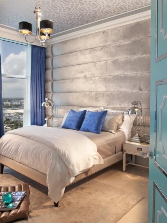 una camera da letto grigio chiaro e argento infusa di blu audace - cuscini e tende di questa tonalità