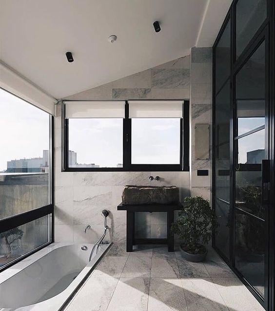 un bagno contemporaneo in nero e neutri, con un lavandino in pietra grezza, una vasca da bagno incassata con una splendida vista panoramica