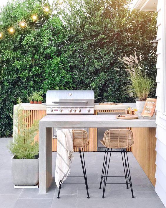 un'elegante cucina esterna con barbecue contemporanea in legno e cemento, con una griglia e una zona cottura, una zona pranzo in cemento e sgabelli in rattan