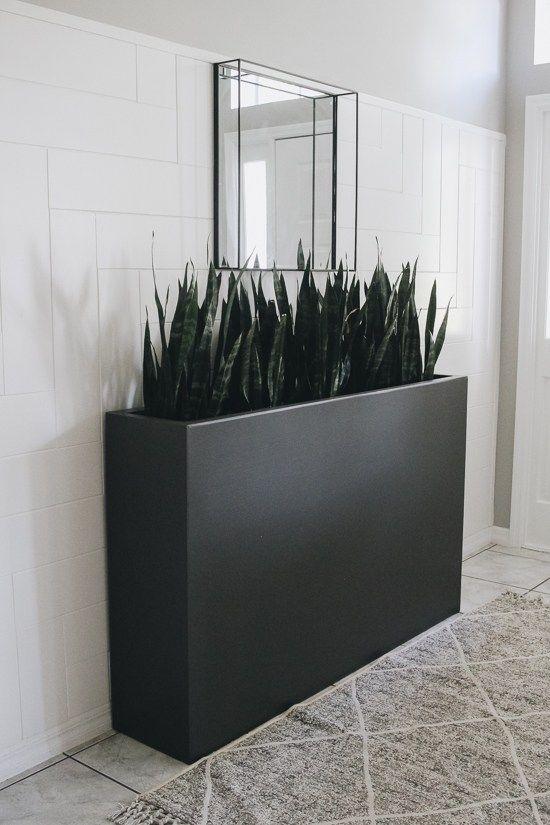 una moderna fioriera nera alta, lunga e stretta accentuerà al meglio qualsiasi spazio interno o esterno