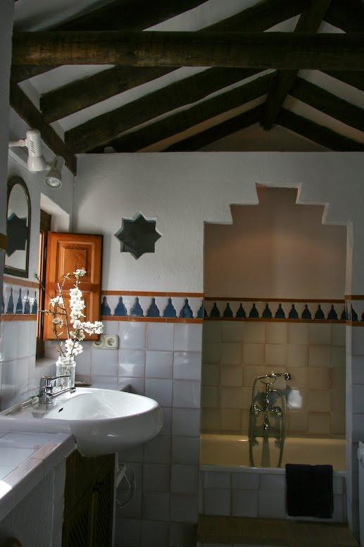 un bagno di ispirazione marocchina con uno spazio doccia ritagliato, piastrelle marocchine e travi in legno e un lavandino bianco