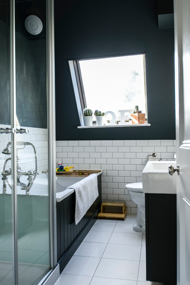 un piccolo ed elegante bagno in mansarda con piastrelle bianche della metropolitana, una vasca da bagno rivestita di nero e un lavabo, una vasca e un lavandino bianchi (Lauren Bryan Knight)