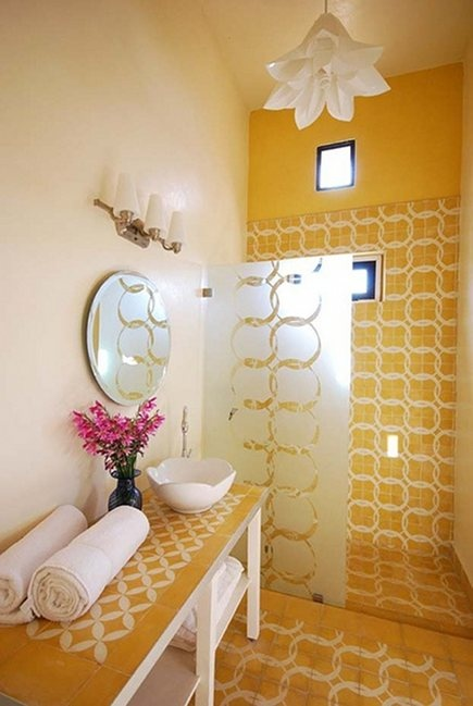 un bagno giallo brillante con piastrelle accattivanti, una lampada a sospensione a forma di fiore e una vanità rivestita di piastrelle