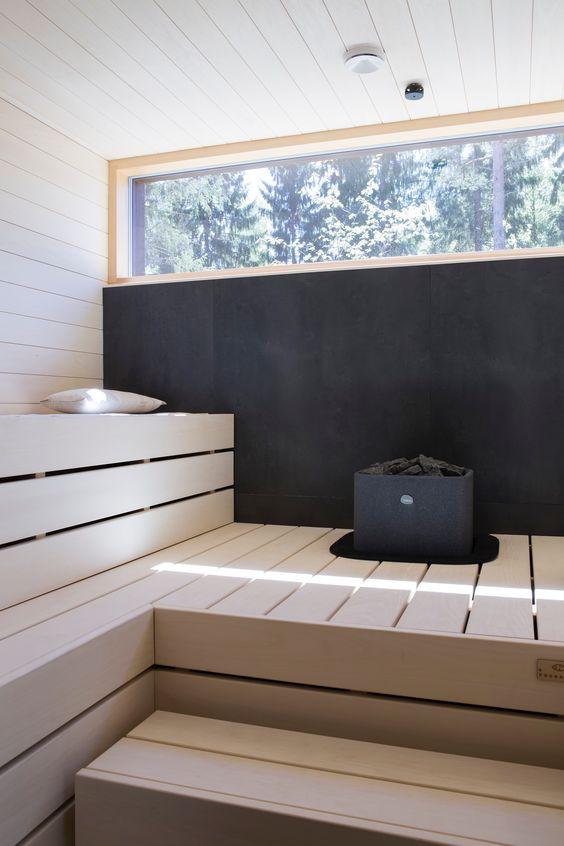 un audace bagno turco con un muro nero, un lucernario e panche in legno sbiancato è super moderno