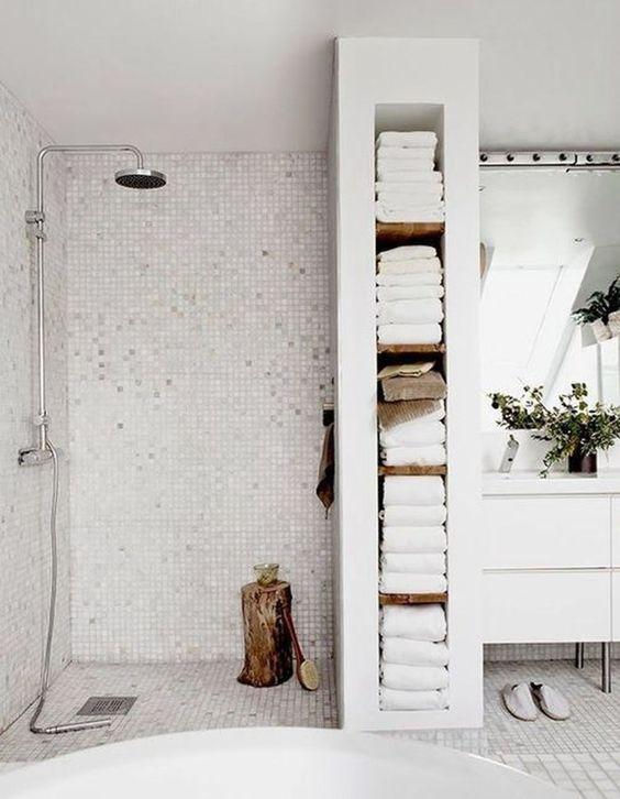 un bagno scandinavo chic e sereno fatto in bianco e bianco sporco, con un ceppo di legno, vegetazione in vaso e spazio di archiviazione integrato