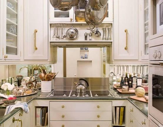 un'elegante piccola cucina con armadi bianchi, hardware dorato, alzatina a specchio, ripiani scuri