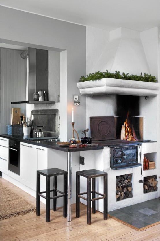 un contemporaneo incontra la cucina scandinava vintage con una stufa, armadi bianchi con un piano di lavoro nero, tocchi di metallo e sgabelli neri