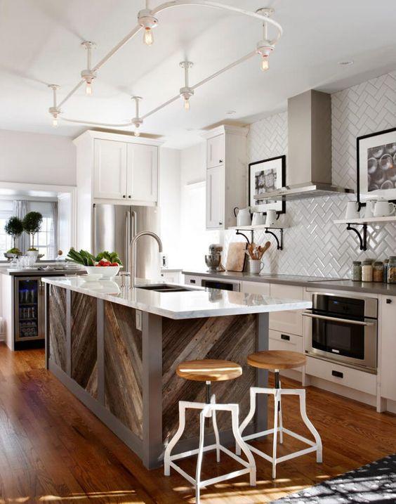 un'isola da cucina rivestita in legno di pallet chevron con un piano di lavoro bianco si distingue in questa cucina neutra e aggiunge un tocco rustico