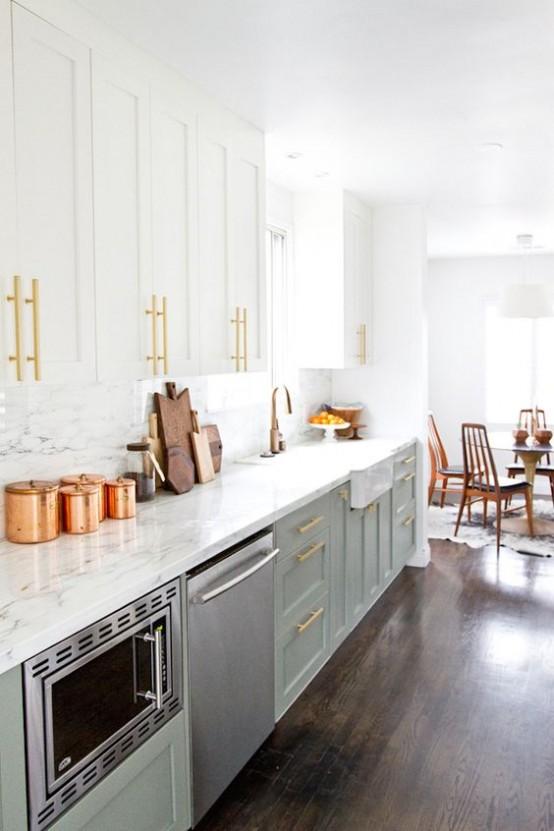 una cucina moderna della metà del secolo verde chiaro e bianco con ripiani in marmo e un alzatina più tocchi d'oro