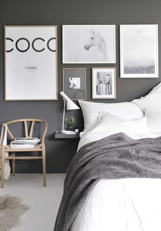 una camera da letto monocromatica audace con un muro scuro, molte opere d'arte, un letto comodo, una sedia e comodini galleggianti