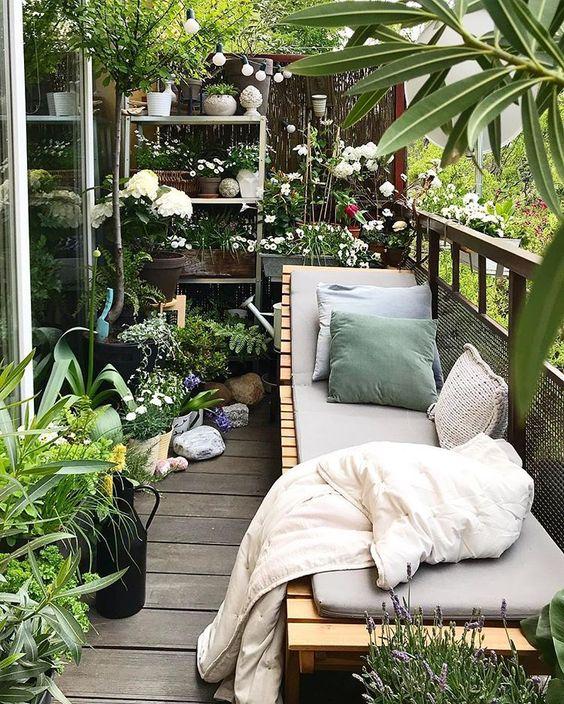 un giardino con balcone con vegetazione in vaso e fiori e un lettino in legno con tappezzeria e cuscini è un posto meraviglioso dove stare